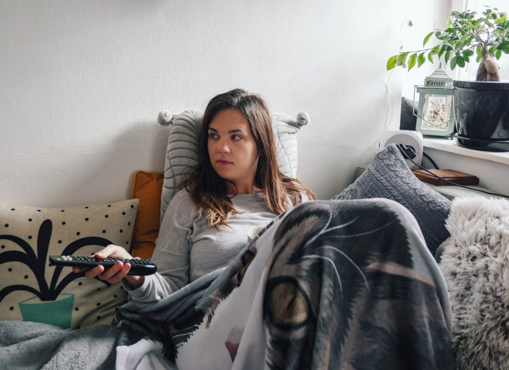 Woman watching TV from bed.