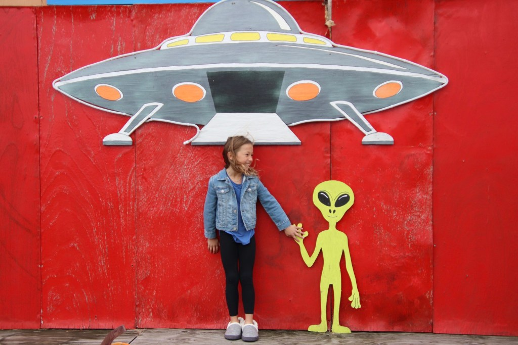 Little girl posing with pained alien.