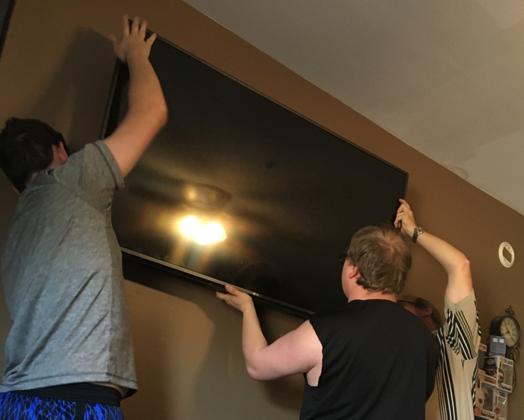 Three men mounting TV together.