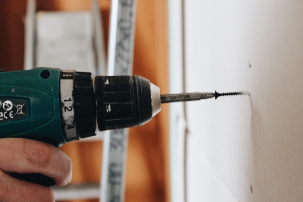 Man drilling screw into the wall.