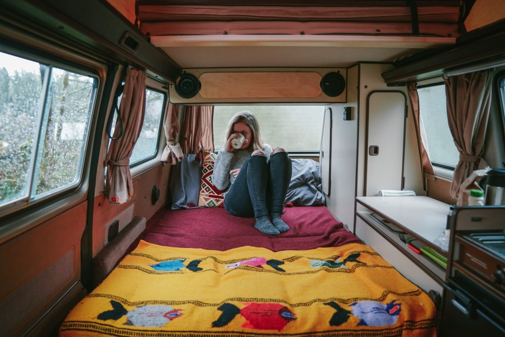 Woman drinking a cup of coffee from within her RV.